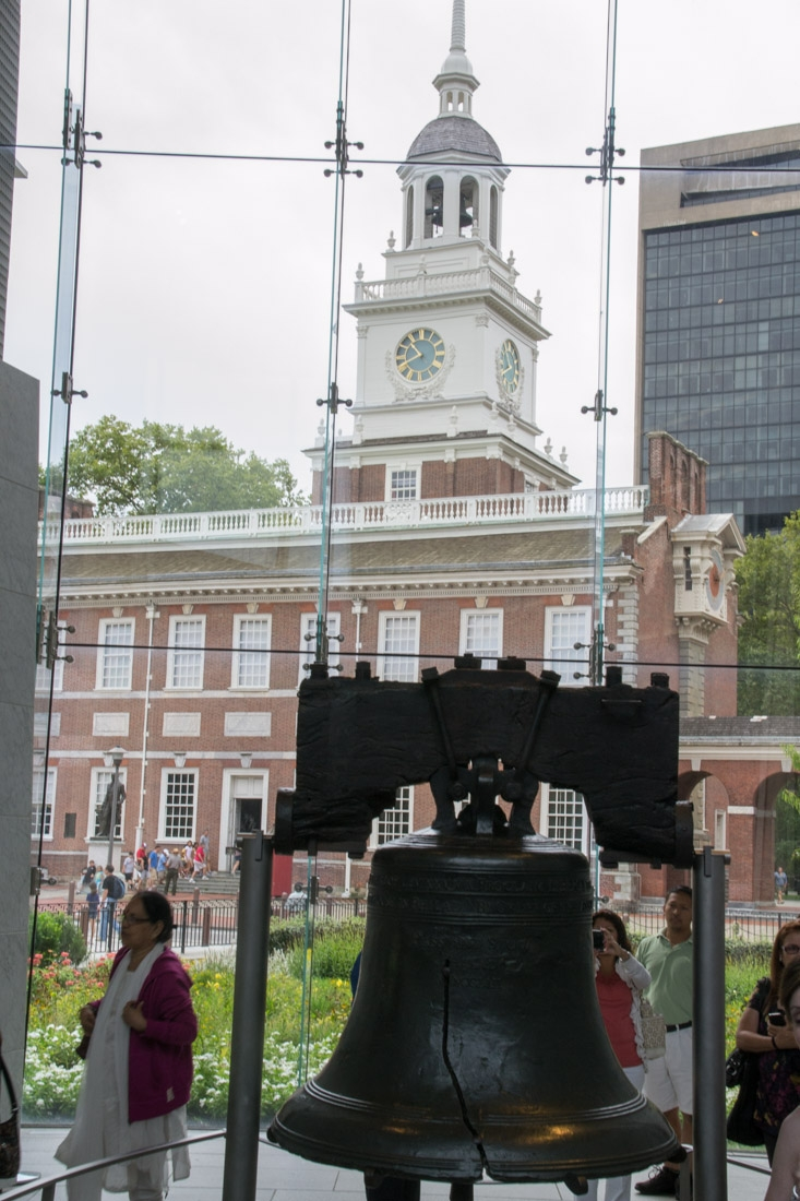 Liberty Bell inside the Liberty Bell Center, and the tall windows that allow you to see the Liberty Bell's original home, the tower of the former Pennsylvania State House (now Independence Hall)